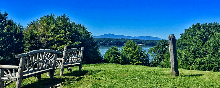 Photograph taken from a hill in the Hudson Valley in NYS with two benches, blue mountains, trees, & water in the background.