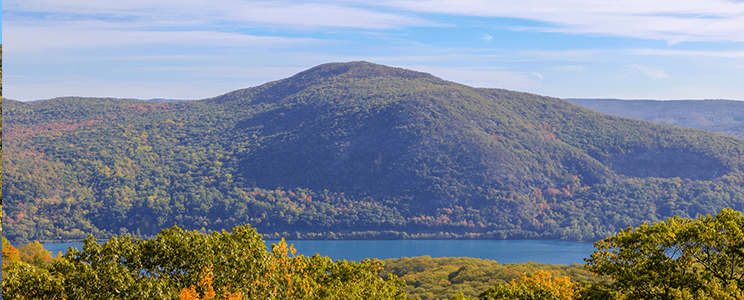 Photograph of the Hudson Valley in NYS in the fall. Colorful trees, water, and mountains can be seen in the distance.