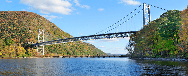 Photograph of a Bridge in the Hudson Valley in NYS surrounded by lush & colorful trees and plants in the fall.